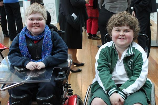 Photo of two children sitting. One of them is on a wheelchair