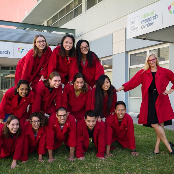 The Brain Autoimmunity Group make a human pyramid wearing their red lab coats to raise awareness for MS.