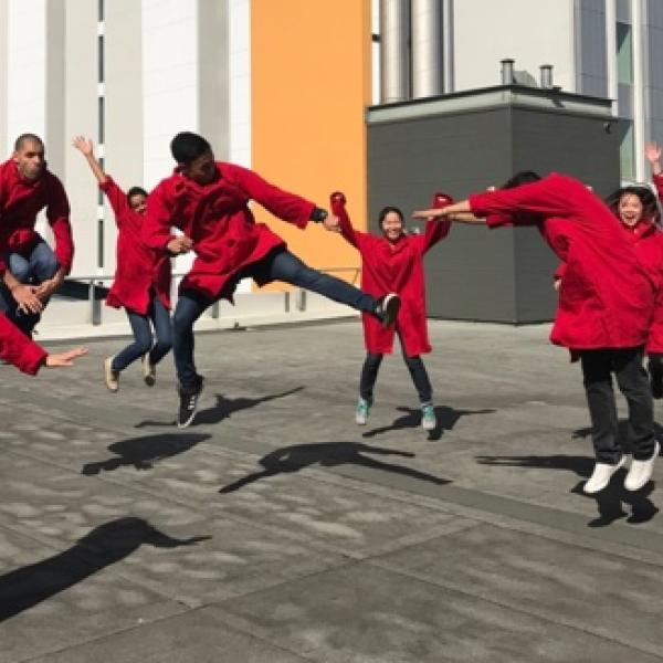Research team members dressed in red overalls jumping for joy