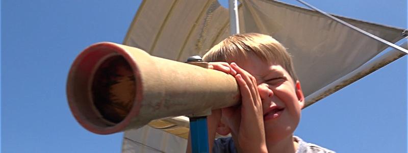 Photo of a child looking through a telescope